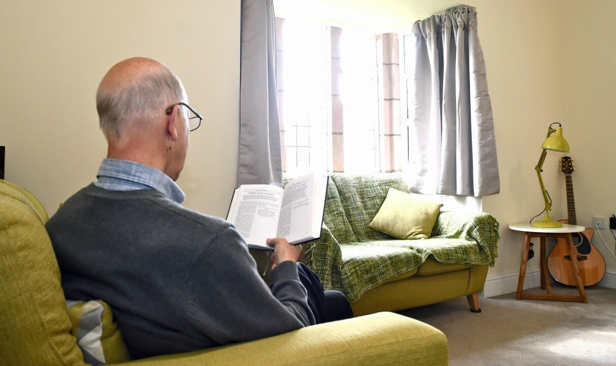 Resident reading in the lounge of a larger cottage