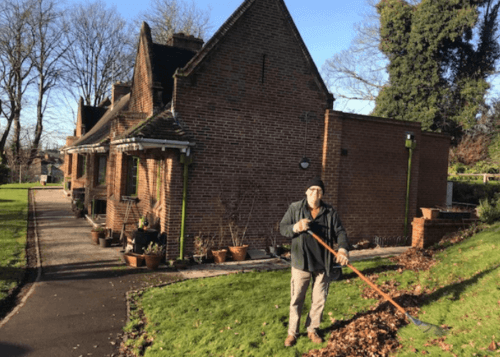 Gardener working at Glover's clearing leaves